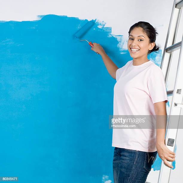 portrait of a young woman painting a wall with a paint roller - step ladder stock photos and pictures