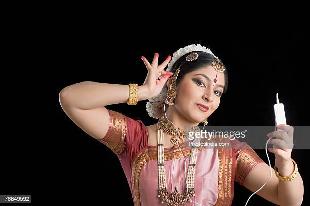 Portrait of a young woman performing Bharatnatyam and listening to an MP3 player