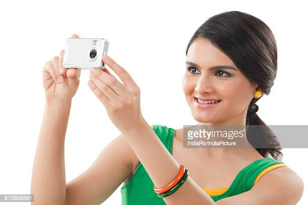 Portrait of a young woman photographing with a digital camera