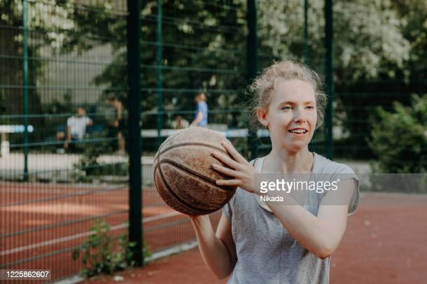 portrait of a young woman playing basketball on the court outdoors - shooting at goal stock pictures, royalty-free photos & images