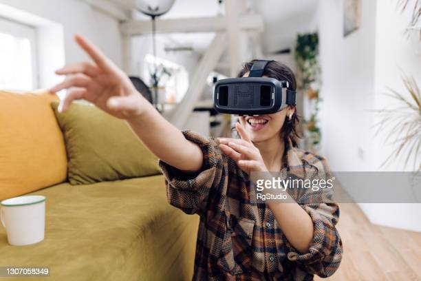 portrait of a young woman playing games using virtual reality glasses - flying goggles stock pictures, royalty-free photos & images