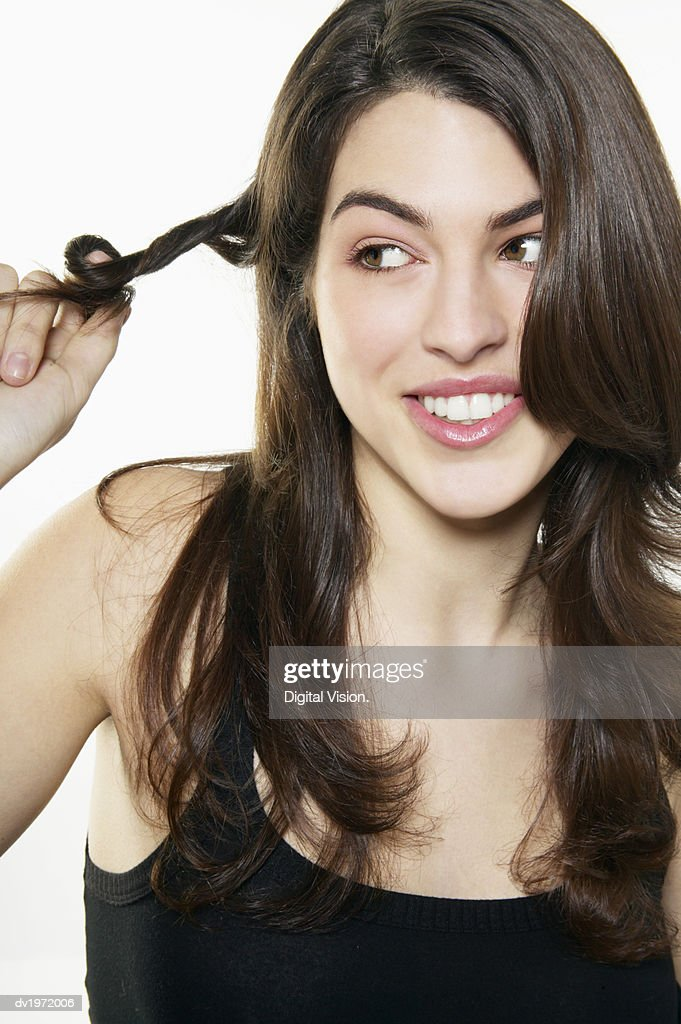Portrait of a Young Woman Playing with Her Hair : Stock Photo