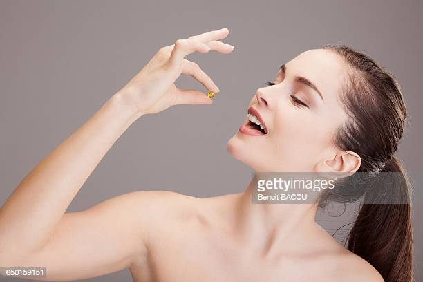 Portrait of a young woman preparing to take a capsule of trace elements