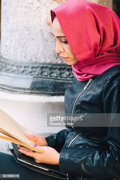Portrait Of A Young Woman Reading A Book Outdoors