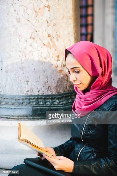 Retrato de una mujer joven lee un libro al aire libre
