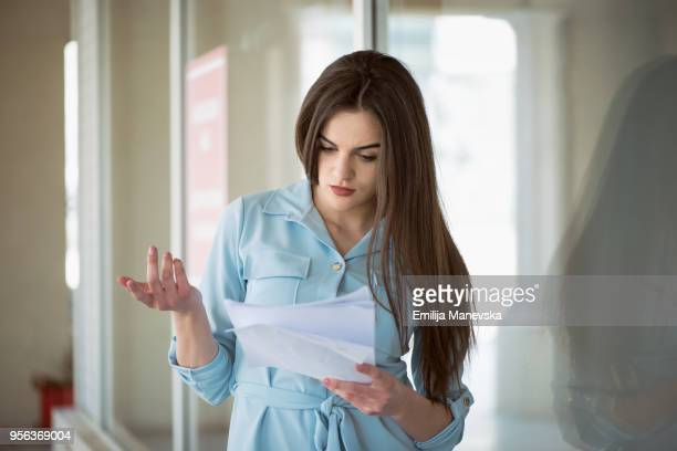 portrait of a young woman reading bad letter - bank statement stock pictures, royalty-free photos & images