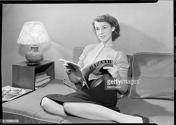 Portrait of a young woman reading Harper's Bazaar. She is shown full-length, seated on a sofa. Photo circa 1950's.