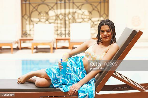 portrait of a young woman reclining on a lounge chair and holding a glass of cocktail - indian bikini stock pictures, royalty-free photos & images