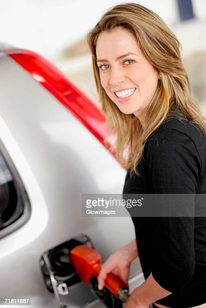 Portrait of a young woman refueling a car