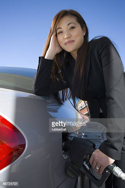 Portrait of a young woman refueling her car and smiling