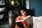 Portrait of a young woman relaxing and reading in her Downtown Los Angeles apartment