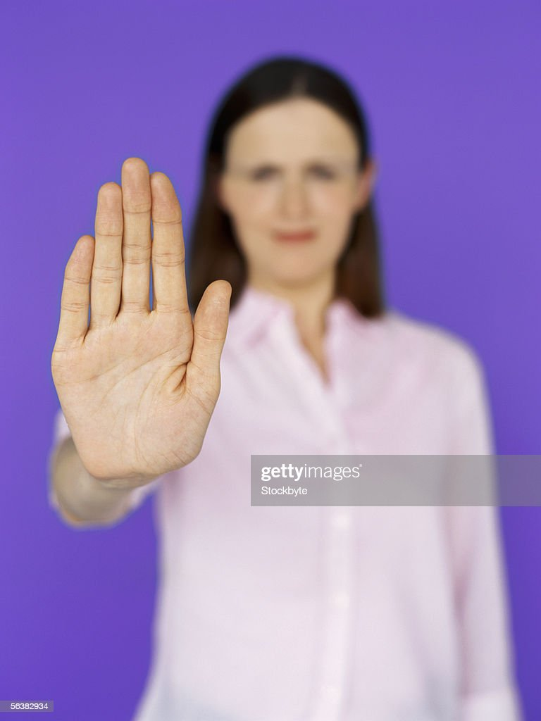 portrait of a young woman showing a stop gesture : Stock Photo