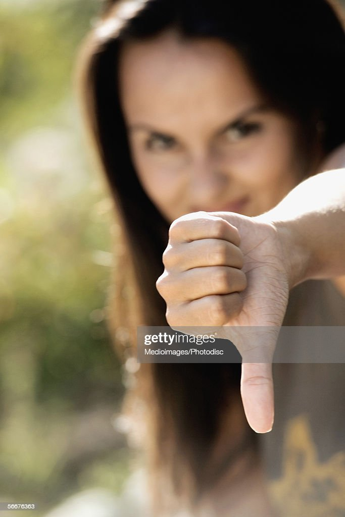 Portrait of a young woman showing a thumbs down sign : Stock Photo