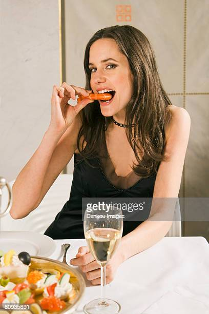 Portrait of a young woman sitting at a table and eating a prawn