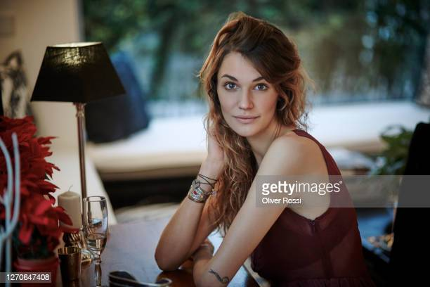 portrait of a young woman sitting at table at home - one young woman only stock pictures, royalty-free photos & images