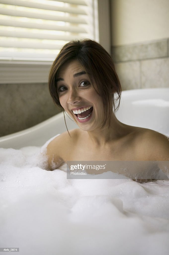 Portrait of a young woman sitting in a bathtub : Foto de stock