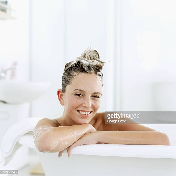 portrait of a young woman sitting in a bathtub with shampoo in her hair