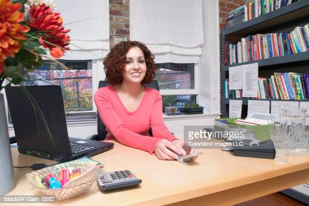 portrait of a young woman sitting in an office smiling - bookend stock pictures, royalty-free photos & images