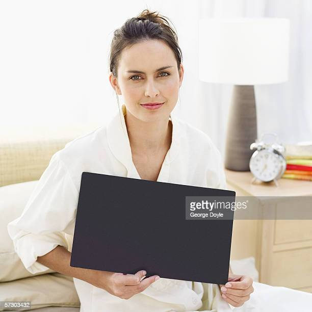 Portrait of a young woman sitting in bed holding black blank board