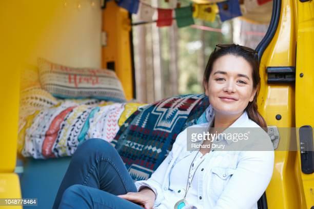 Portrait of a young woman sitting in the doorway of her camper van