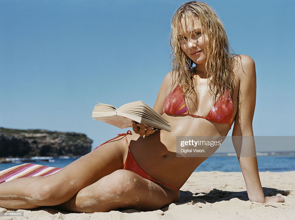 Portrait of a Young Woman Sitting on a Beach and Holding a Book : Stock Photo