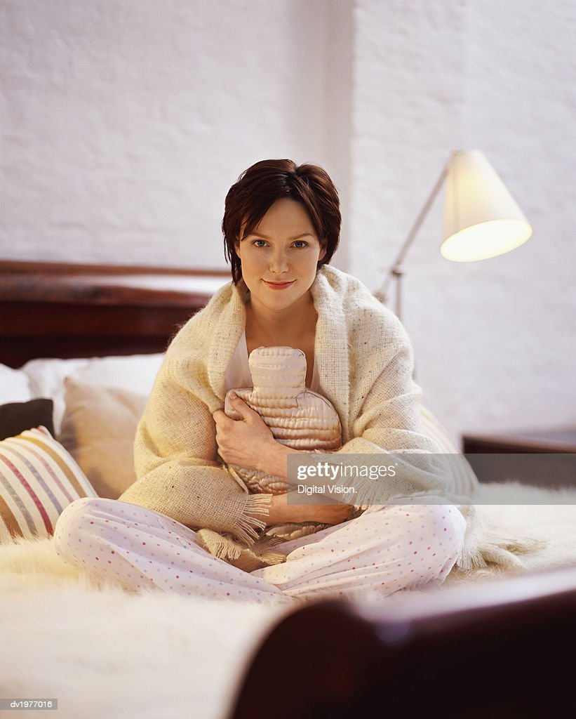 Portrait of a Young Woman Sitting on a Bed and Holding a Hot Water Bottle : Stock Photo