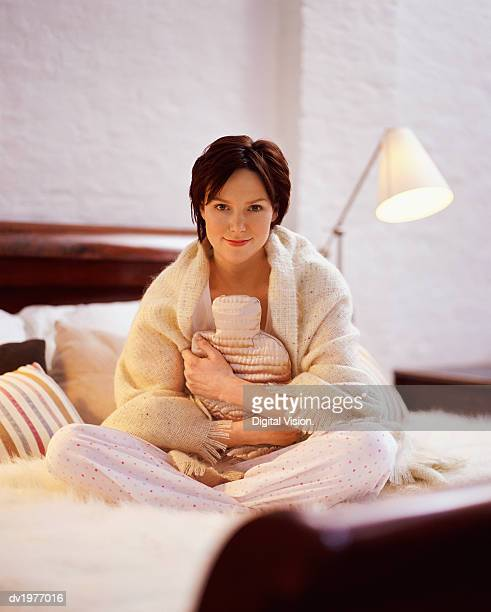 Portrait of a Young Woman Sitting on a Bed and Holding a Hot Water Bottle