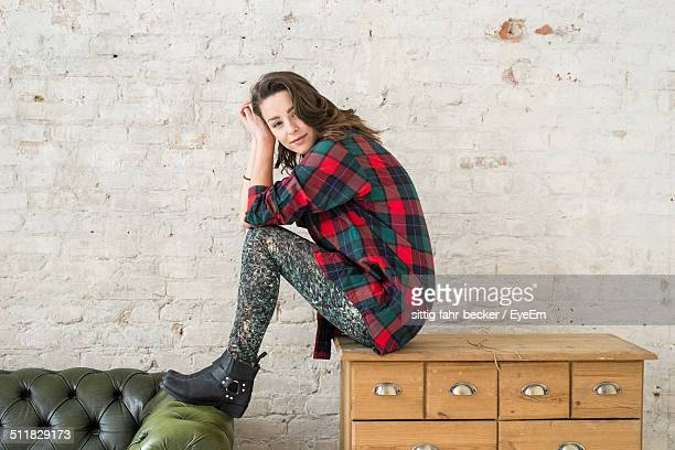 portrait of a young woman sitting on a cabinet - white boot stock pictures, royalty-free photos & images