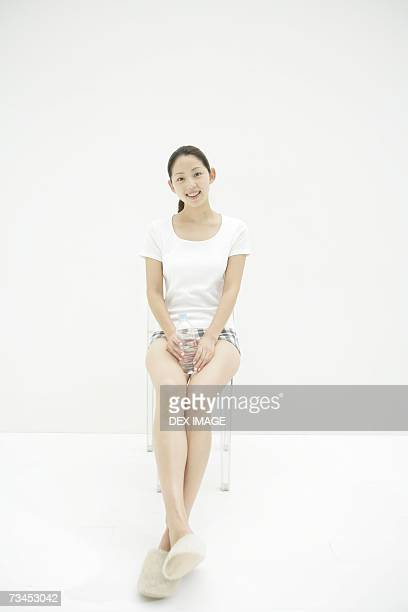 Portrait of a young woman sitting on a chair and holding a water bottle