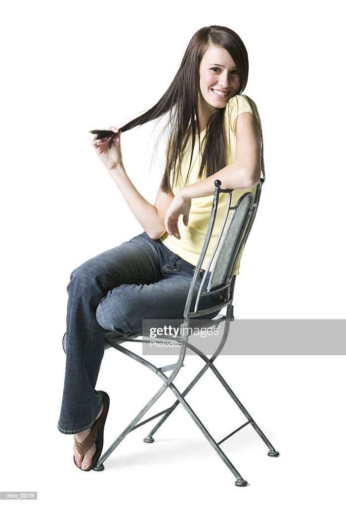 Portrait of a young woman sitting on a chair : Foto de stock