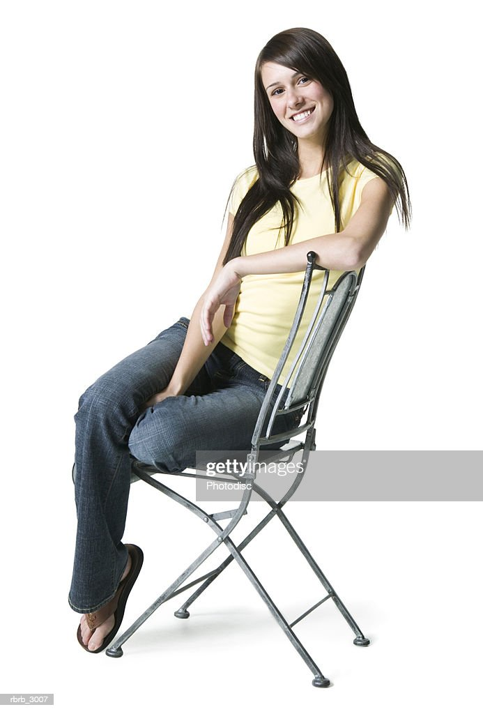 Portrait of a young woman sitting on a chair smiling : Foto de stock