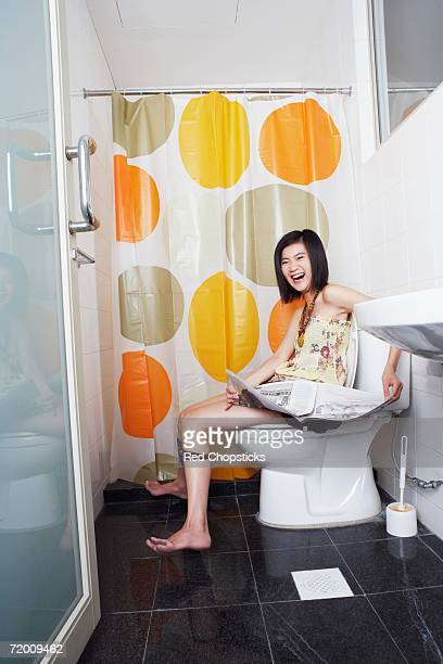 Portrait of a young woman sitting on a toilet bowl and holding a newspaper
