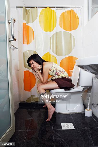 Portrait of a young woman sitting on a toilet bowl