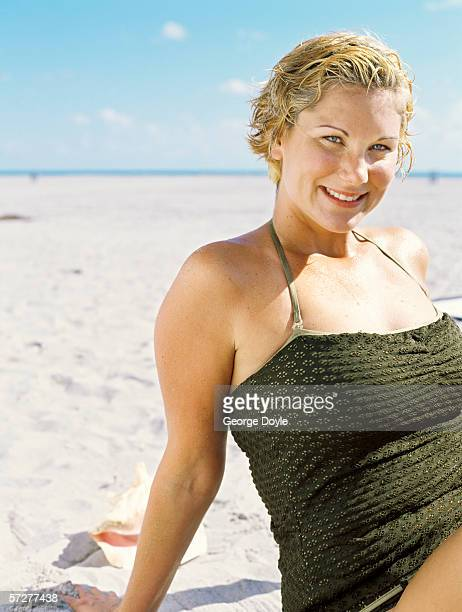 portrait of a young woman sitting on the beach and sunbathing - dicke frauen am strand stock-fotos und bilder