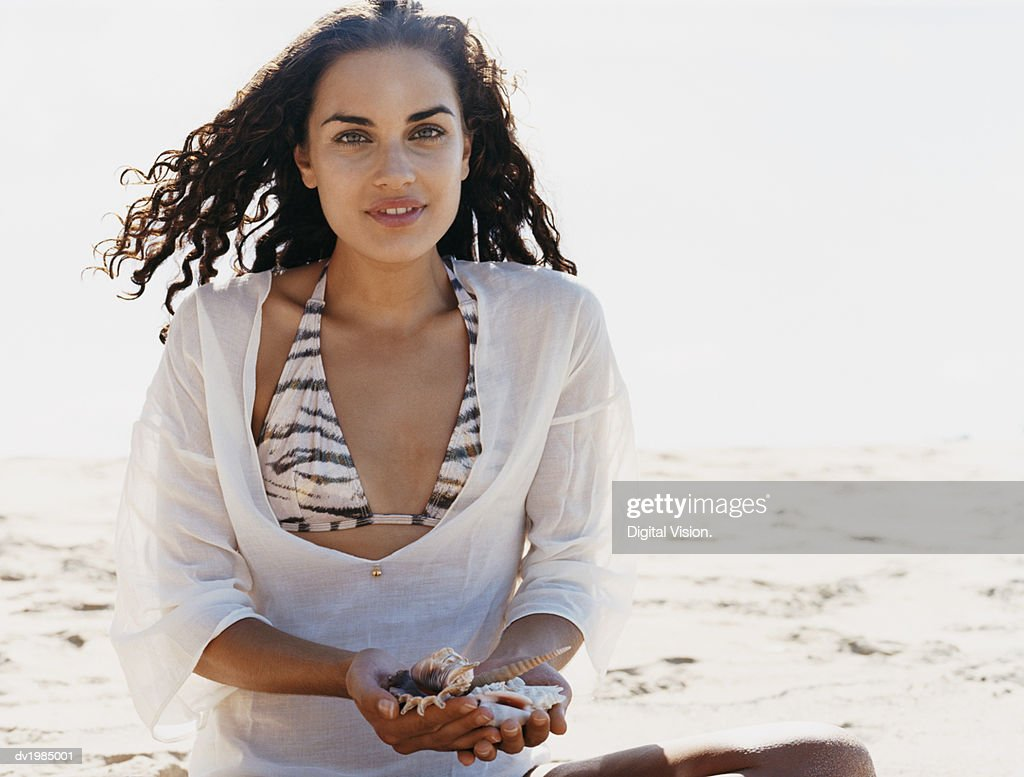 Portrait of a Young Woman Sitting on the Beach Holding Seashells : Stock Photo