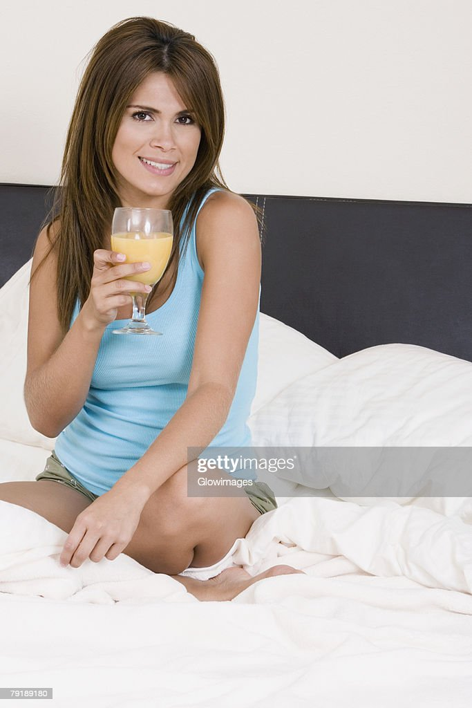 Portrait of a young woman sitting on the bed and holding a glass of orange juice : Foto de stock
