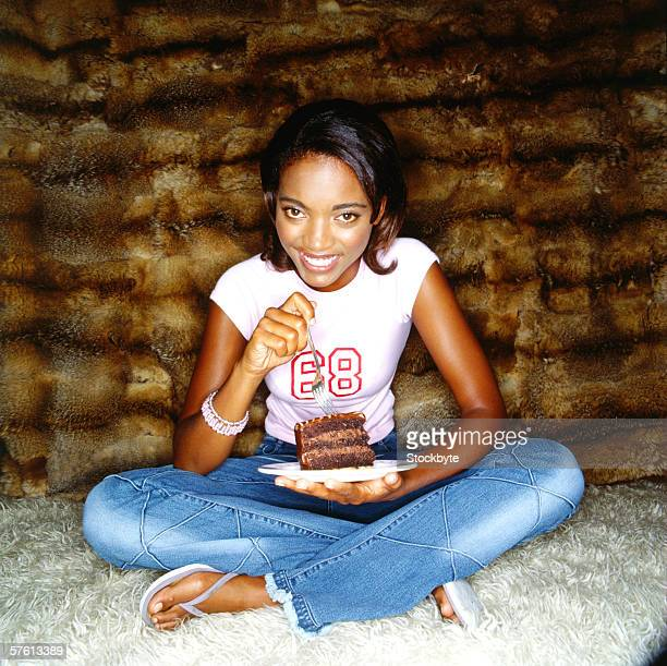 Portrait of a young woman sitting on the floor eating a slice of chocolate cake