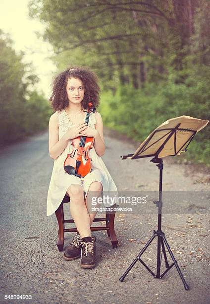 Portrait of a young woman sitting with her violin