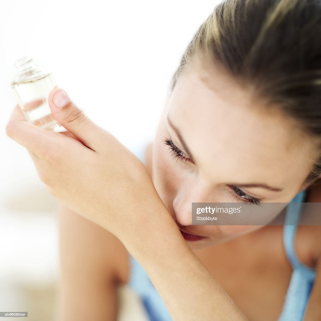 portrait of a young woman smelling perfume on her wrist : Stock Photo