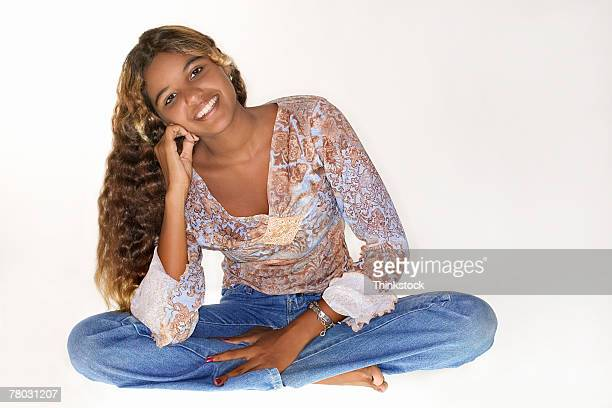 portrait of a young woman smiling as she sits with crossed legs on a white background. - thinkstock stock-fotos und bilder