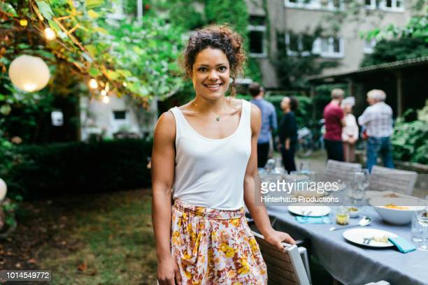 portrait of a young woman smiling at family bbq - sleeveless top stock pictures, royalty-free photos & images