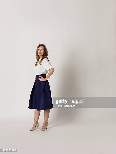 portrait of a young woman smiling - white skirt stock photos and pictures