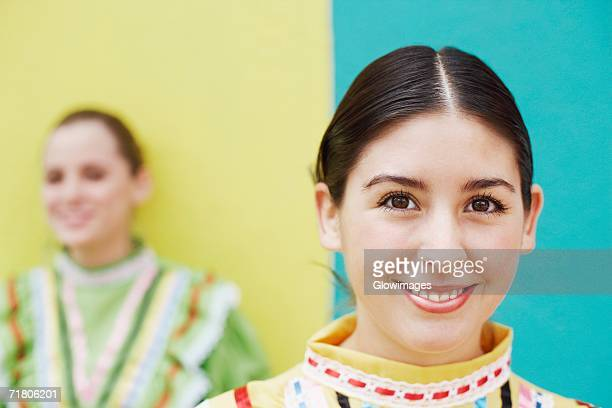 portrait of a young woman smiling with another young woman standing in the background - hair part stock pictures, royalty-free photos & images