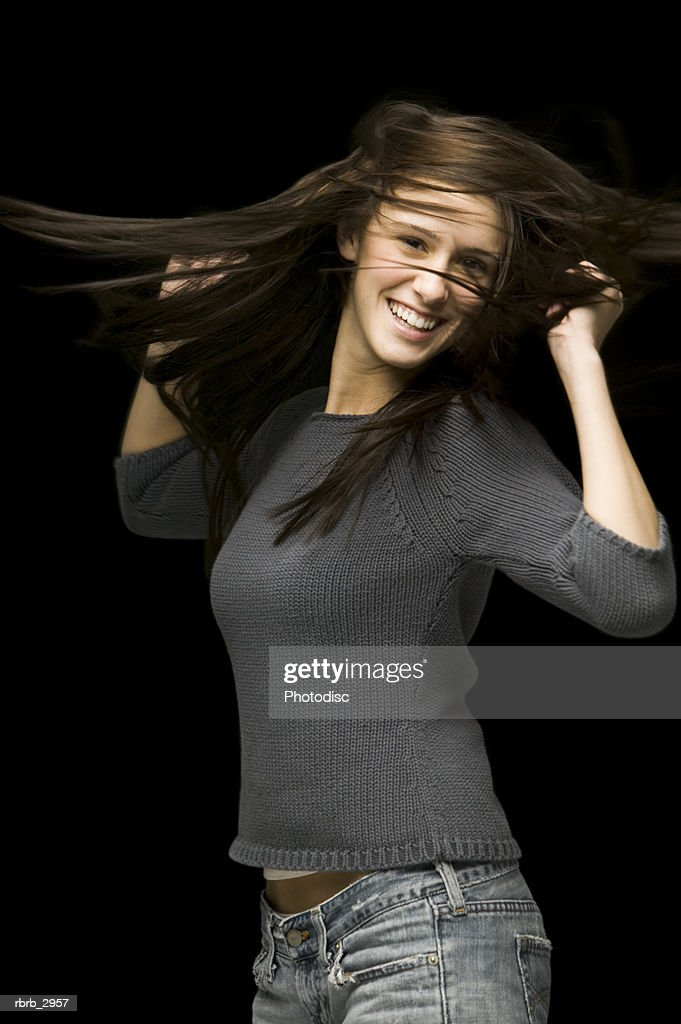 Portrait of a young woman smiling with her arms raised : Foto de stock