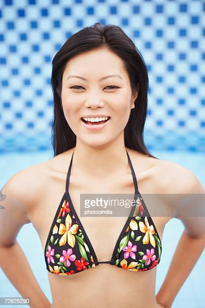 portrait of a young woman smiling with her hands behind her back - indian bikini stock pictures, royalty-free photos & images