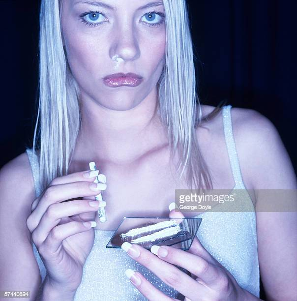 portrait of a young woman snorting drugs