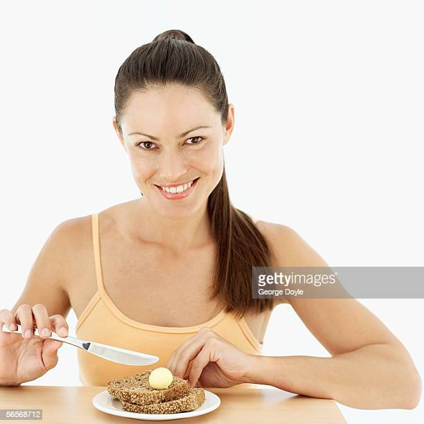 portrait of a young woman spreading butter on brown bread