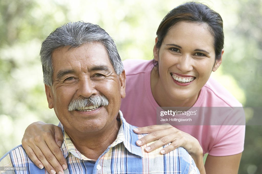 Portrait of a young woman standing behind her father : Stock Photo