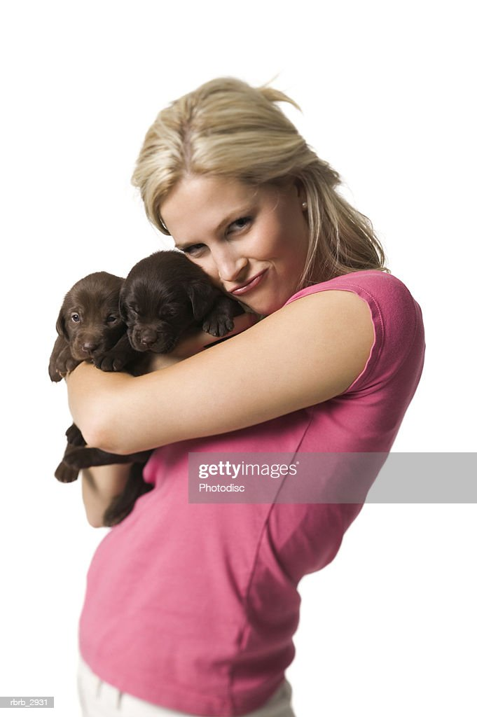 Portrait of a young woman standing holding two puppies : Foto de stock