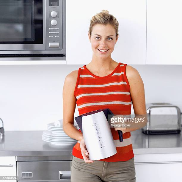 Portrait of a young woman standing in a kitchen holding an electric kettle
